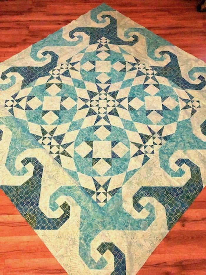 1-unsandwiched snails trail + storm at sea quilt top wooden floor