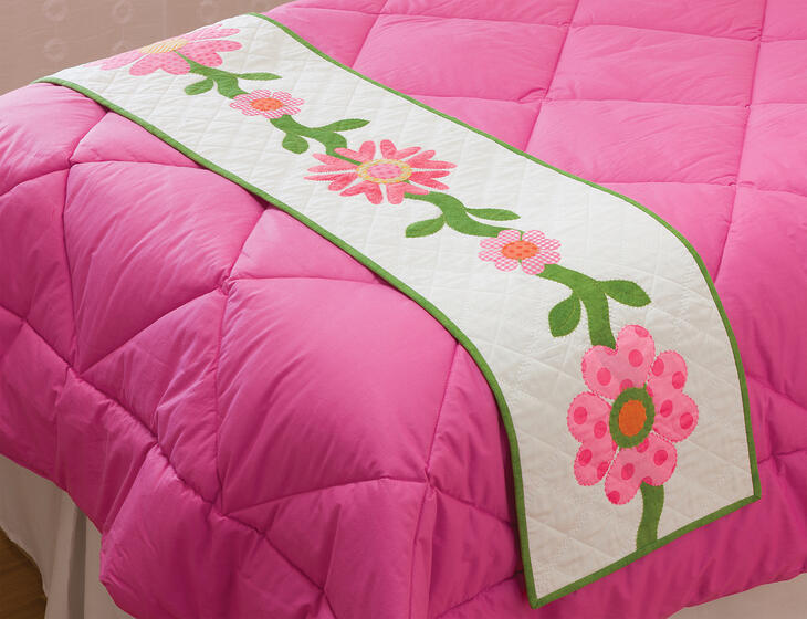 white quilted bed runner with pink flowers made of hearts on a bed with a pink duvet