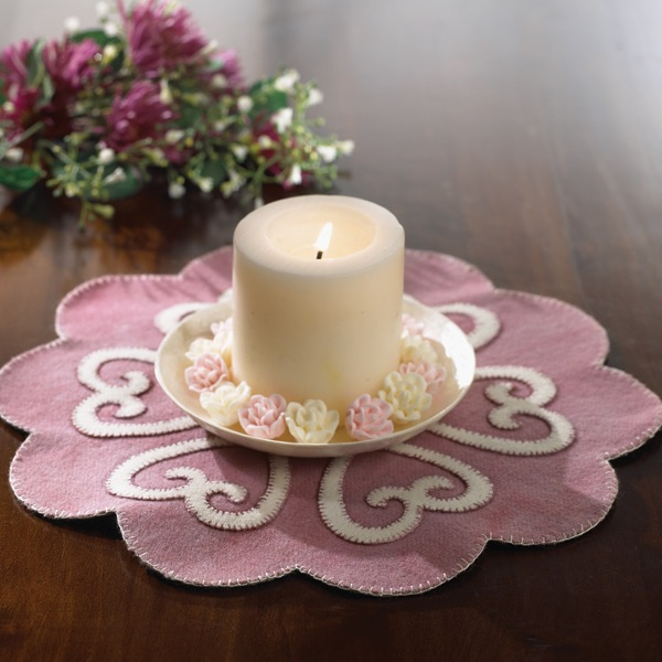 a cream pillar candle sitting on top of a pink suede candle mat with light pink hearts on the center of a wooden table
