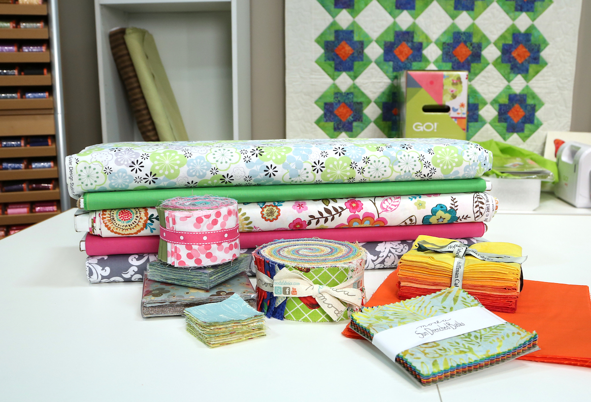 piles of fabric precuts jelly rolls fat quarter stack and layer cakes on sewing table