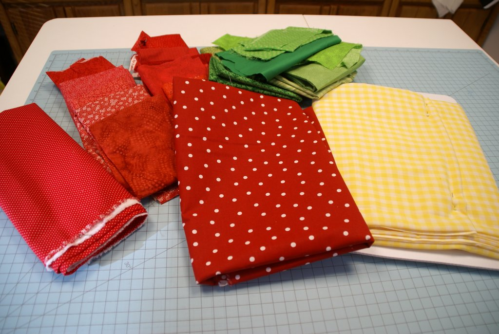 assortment of fabric in red, green and yellow gingham on cutting mat