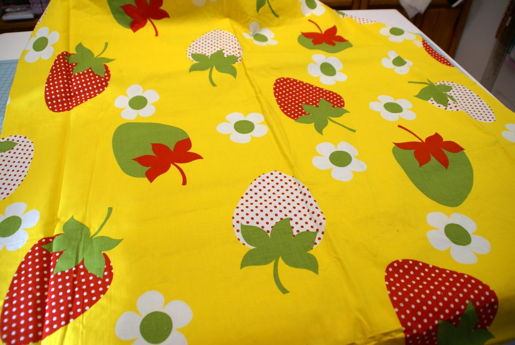 green, red and white polka dot strawberries on yellow fabric