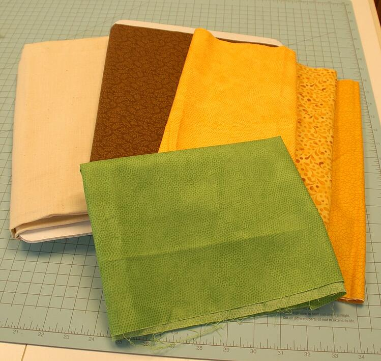 quilt cotton fabric in green, brown and various shades of yellow on a self-healing quilting cutting mat