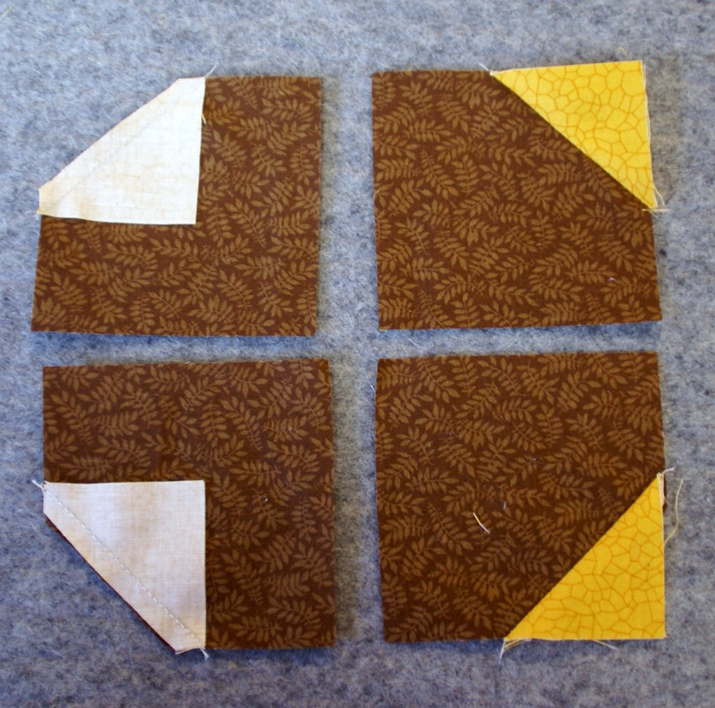 sunflower center block with brown fabrics and yellow corners on wool pressing mat