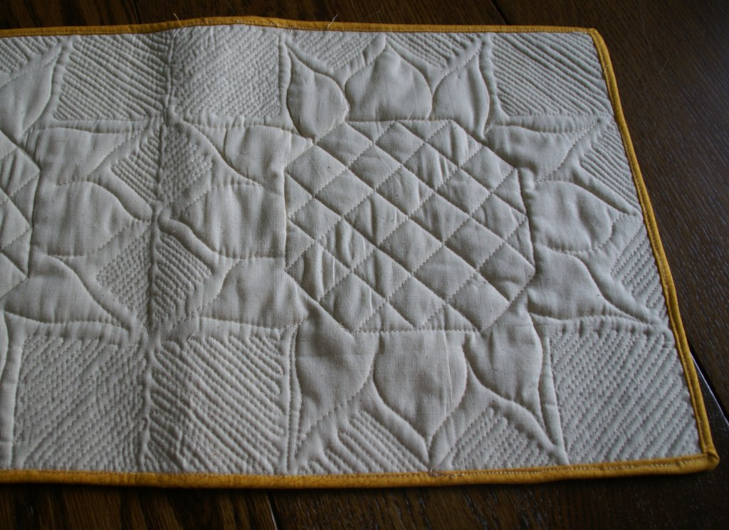 back of sunflower quilt with quilting creating a sunflower shape on the back of the quilt