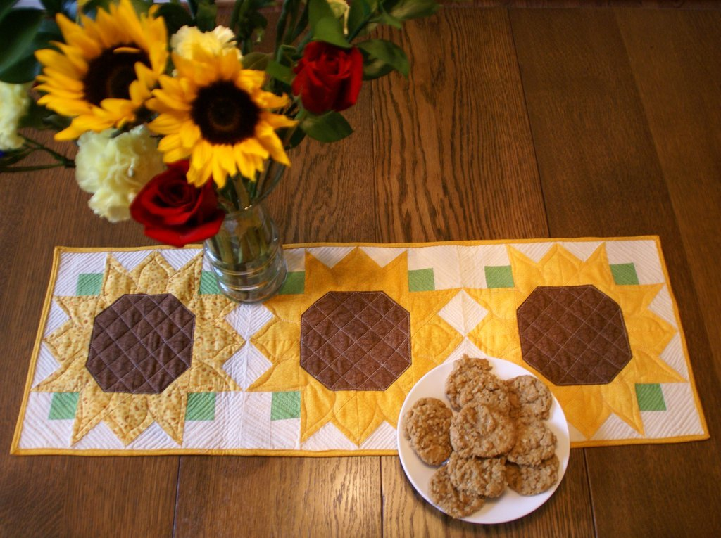 quilted sunflower table runner with a fall bouquet in a vase and oatmeal sunflower seed cookies
