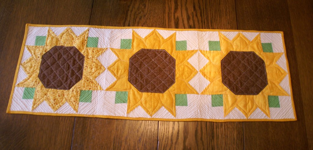 completed sunflower quilted table runner on wooden table