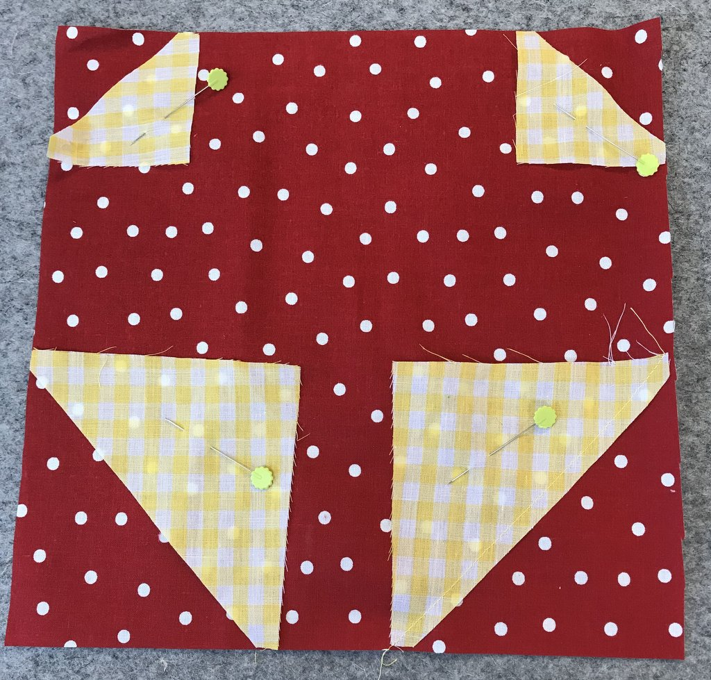 red fabric with white polka dots with yellow gingham fabric pinned in corners