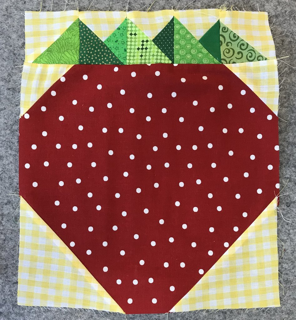 red and white polka dot strawberry block with green top