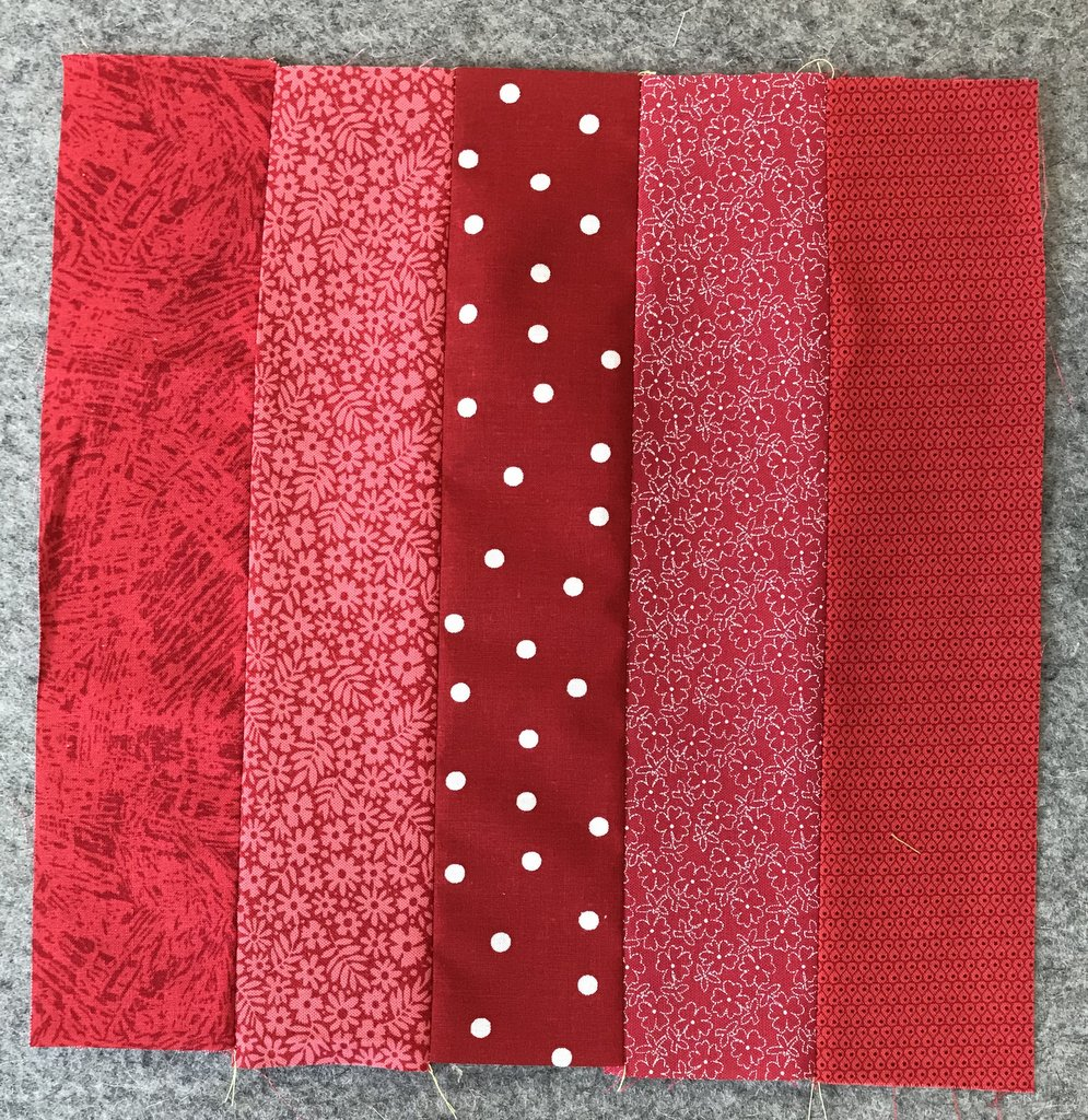 scrappy red fabrics sewn in strips