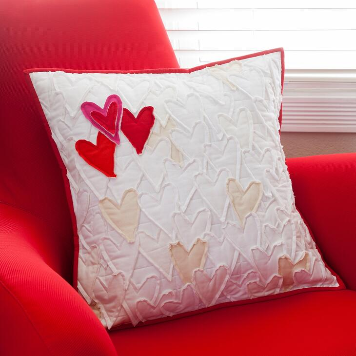 white pillow with appliqued hearts in white, creams and reds on a red accent chair by a window