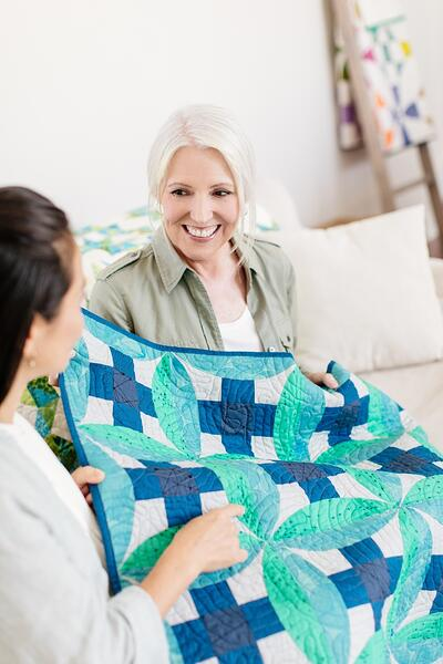 A quilt owner inspects a quilt with another person.