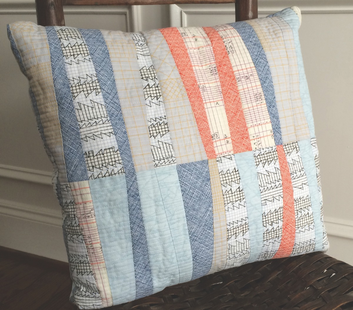 Scrappy throw pillow made with wedge shapes on a wooden chair.
