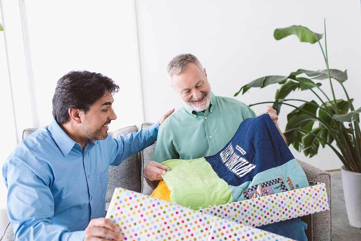 two men unwrapping gift of MemoryStitch t shirt quilt