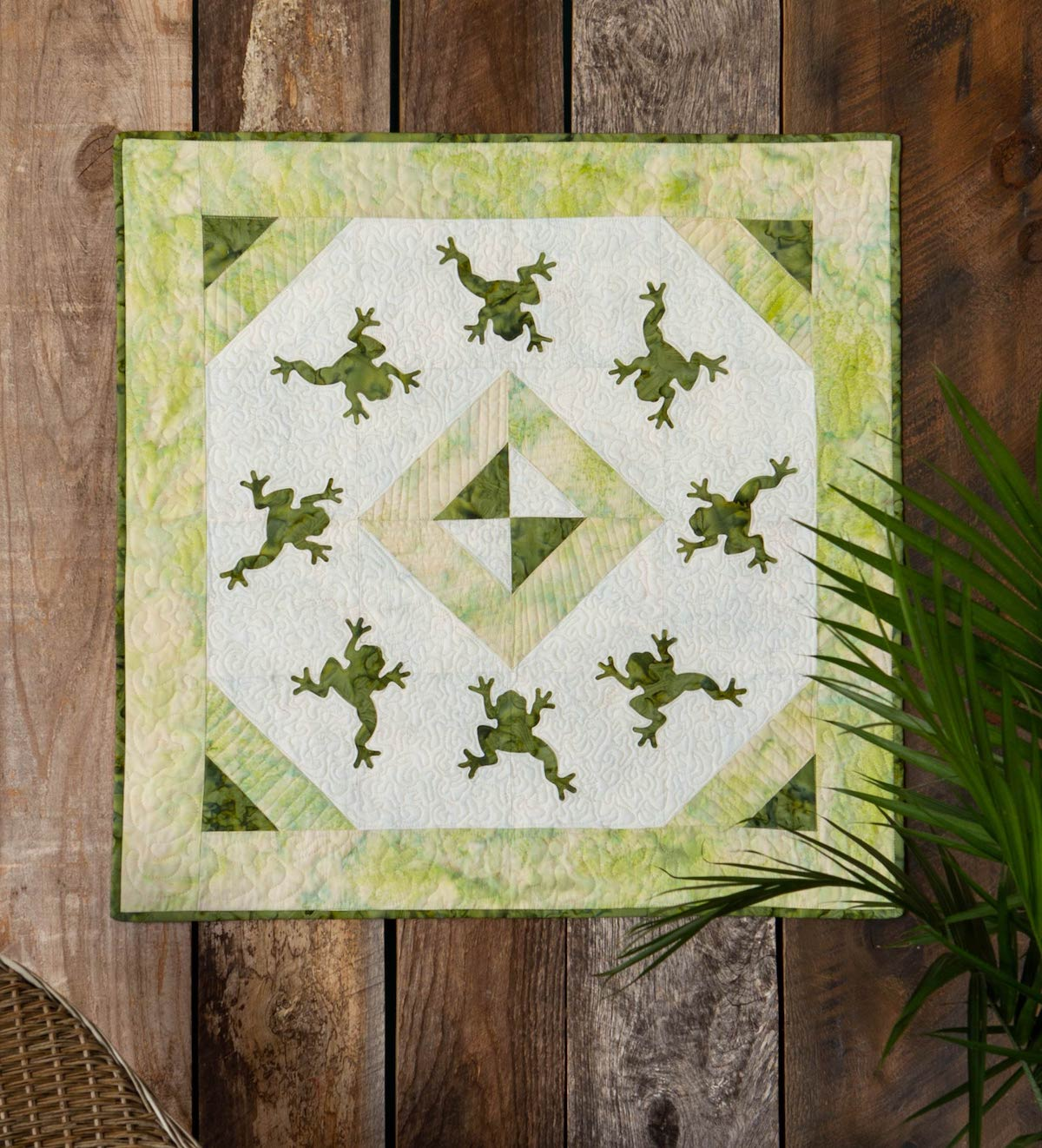 lime, cream and dark green batik wall hanging quilt with multiple frogs facing in a circle an on point square in the middle hanging on a wood panel wall