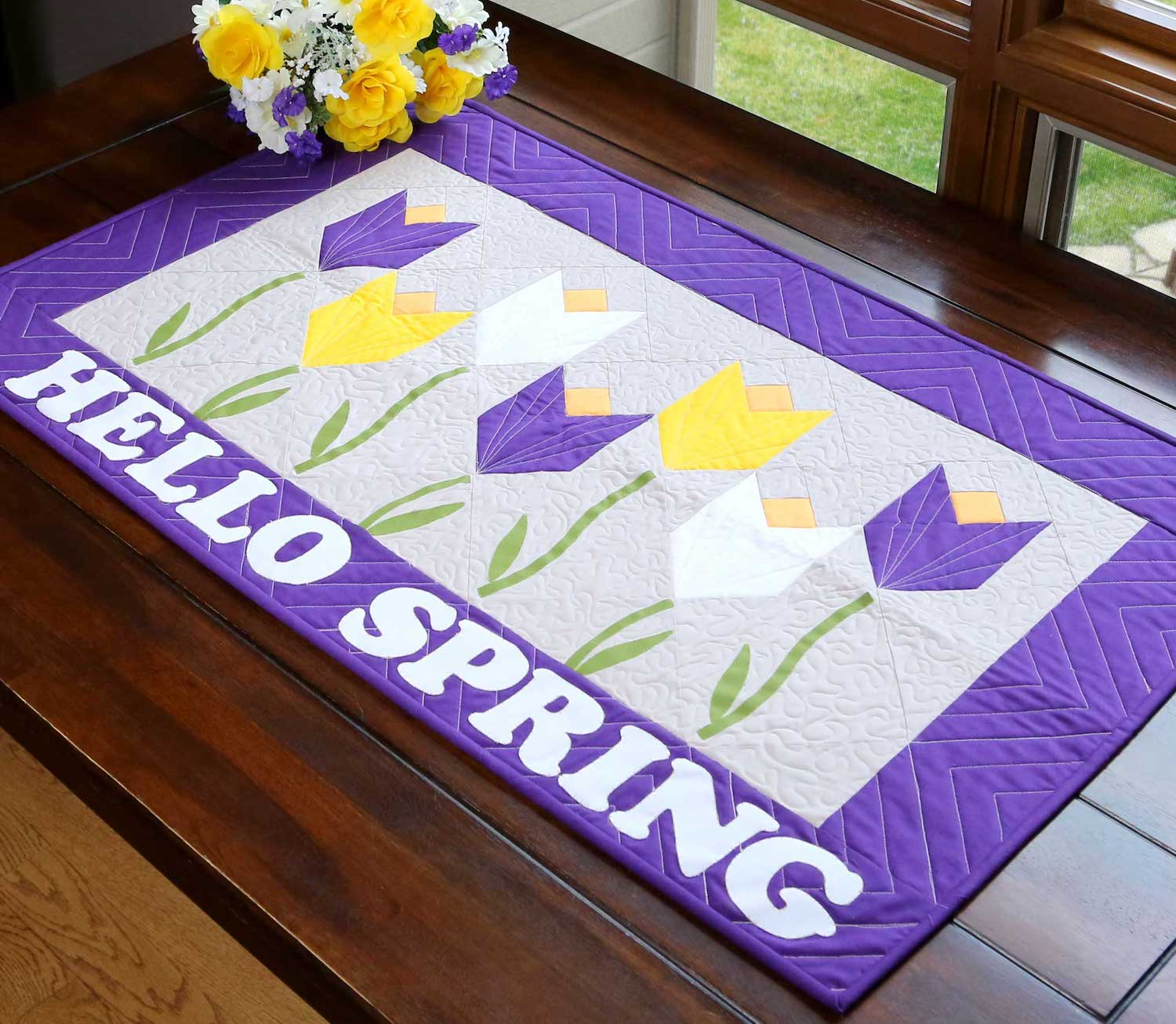 Yellow and purple quilted table runner with tulips and Hello Spring appliqued.