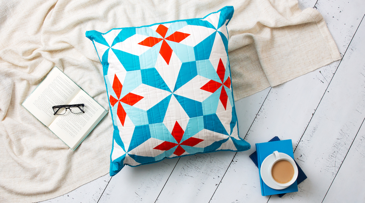 Red, teal and white Hattie's Choice pattern quilted pillow on a white wood floor next to coffee, a blanket, a book and glasses.