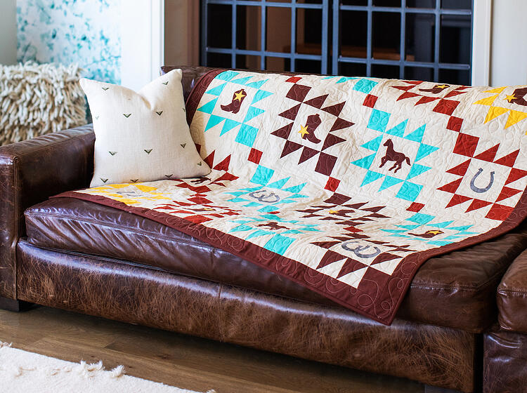 quilt with horse, horseshoe and cowboy boot applique on brown leather couch in living room