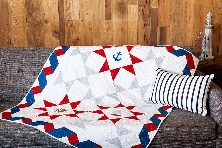 pieced red, white, grey and blue quilt with nautical applique shapes on grey couch with wooden background