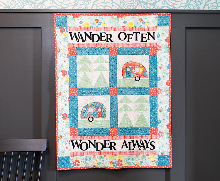 go wander go camper quilt patter with message Wander Often, Wonder Always hanging on wall.