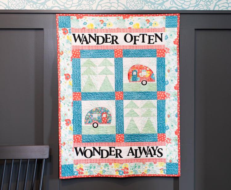 go wander go camper quilt patter with message Wander Often, Wonder Always hanging on wall.