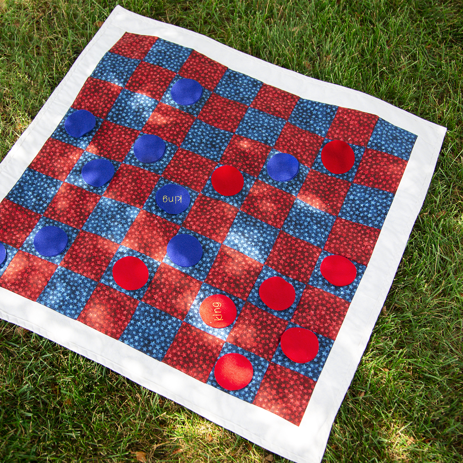 red white and blue homemade fabric checkerboard laying on grass with circular felt checker pieces
