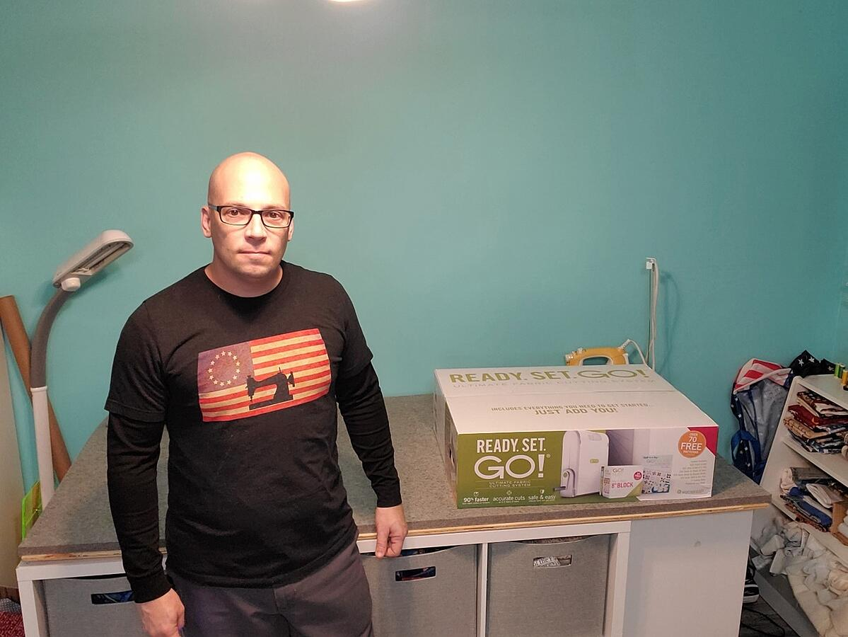 Andrew stands in his ironing space next to the Ready. Set. GO! box preparing to unbox its contents.