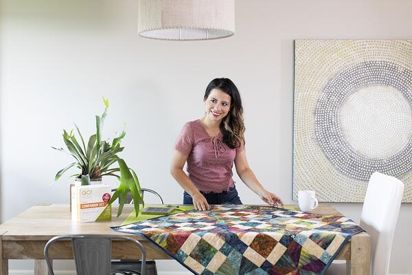 A person standing and smiling next to a quilt on a table.