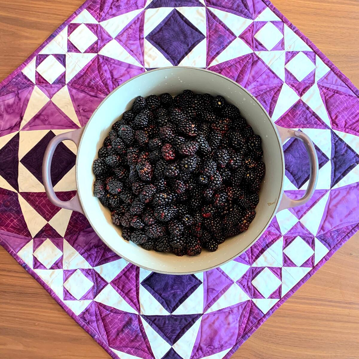 Storm at Sea quilt with pan of blackberries.