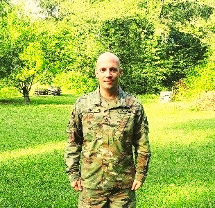 Andrew Lee stands at attention in his US Army uniform. He is outside on a sunny day.