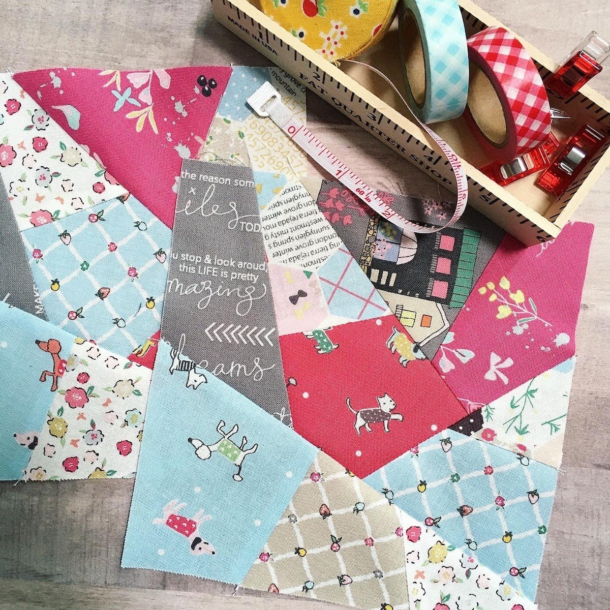 two sewn crazy quilt block six inch finished blocks on concrete table next to printed washi tape quilting clips and sewing ruler