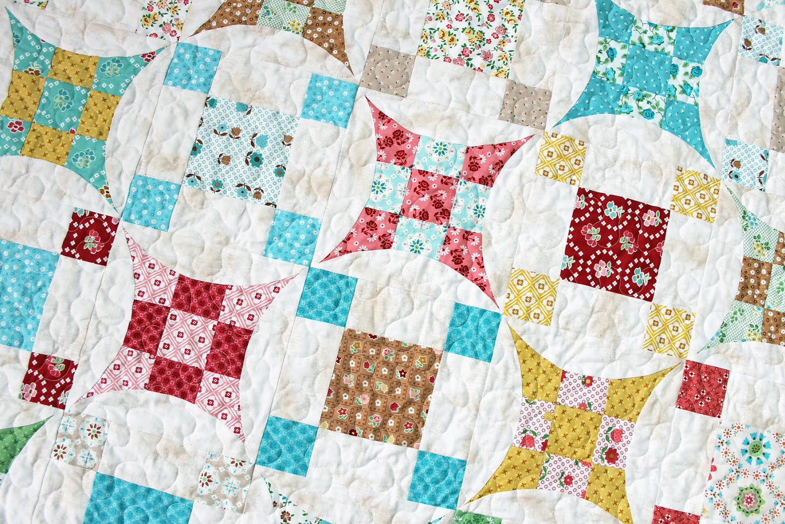 Glorified Nine Patch quilt with red, gold, teal and white fabric.