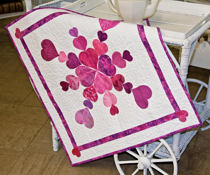 quilted table runner with queen of hearts go die shapes in pink batik fabrics draped over a wicker bar cart