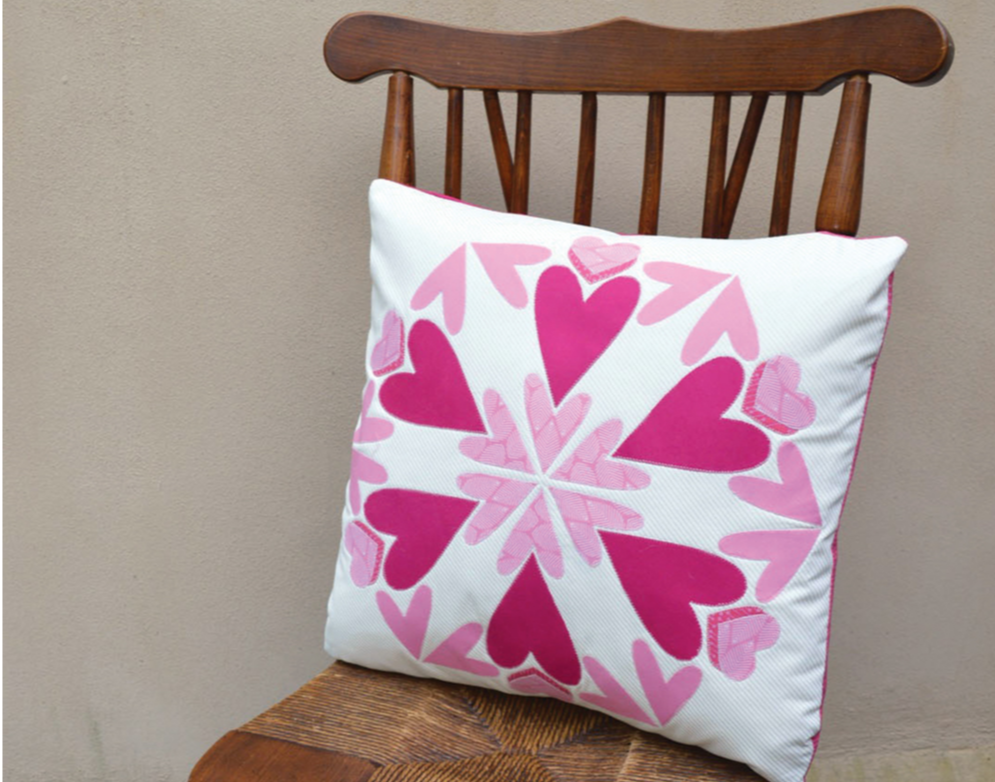 white and pink quilted pillow with hearts making an abstract mandala sitting on wooden chair