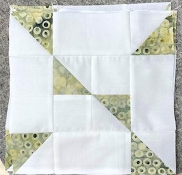 accuquilt half square triangle chain block with white and green and yellow batiks