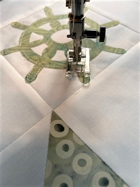 close up of accuquilt ship's wheel fabric applique piece on white block center with sewing machine straight stitching edges