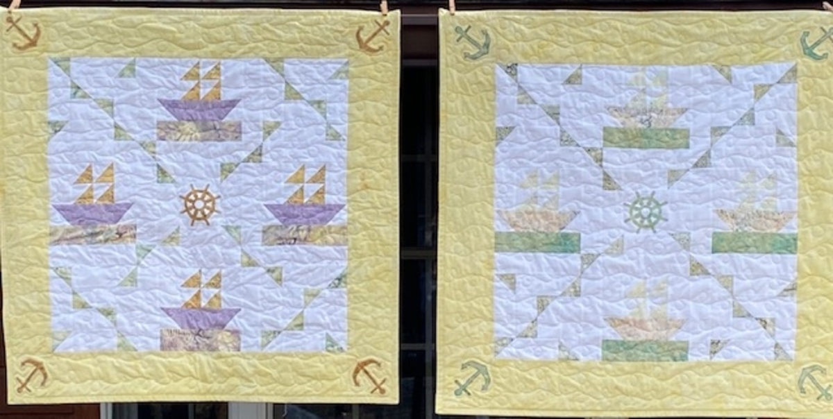 two side by side pieced sailboat baby quilt in different color variations, one with green and yellow and the other in purple and yellow