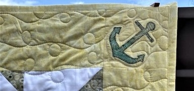 close up of finished baby quilt with accuquilt go! nautical medley anchor applique corner piece with curly quilting
