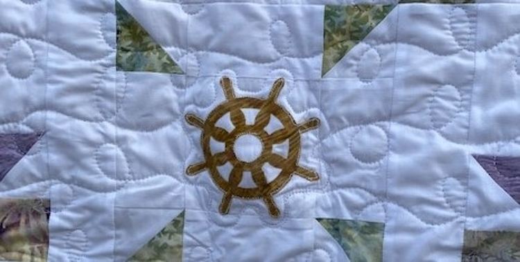 close up of ship's wheel appliqued to the center of baby quilt with curly quilting