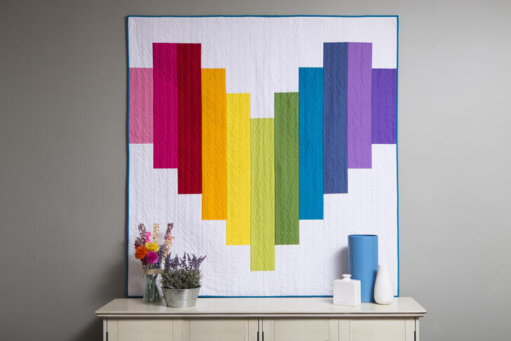 quilt made of rainbow strips in the shape of a heart on a grey wall above a white table