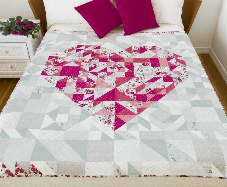 pink, grey and white pieced quilt with heart made of various sized triangles on a bed in a bedroom