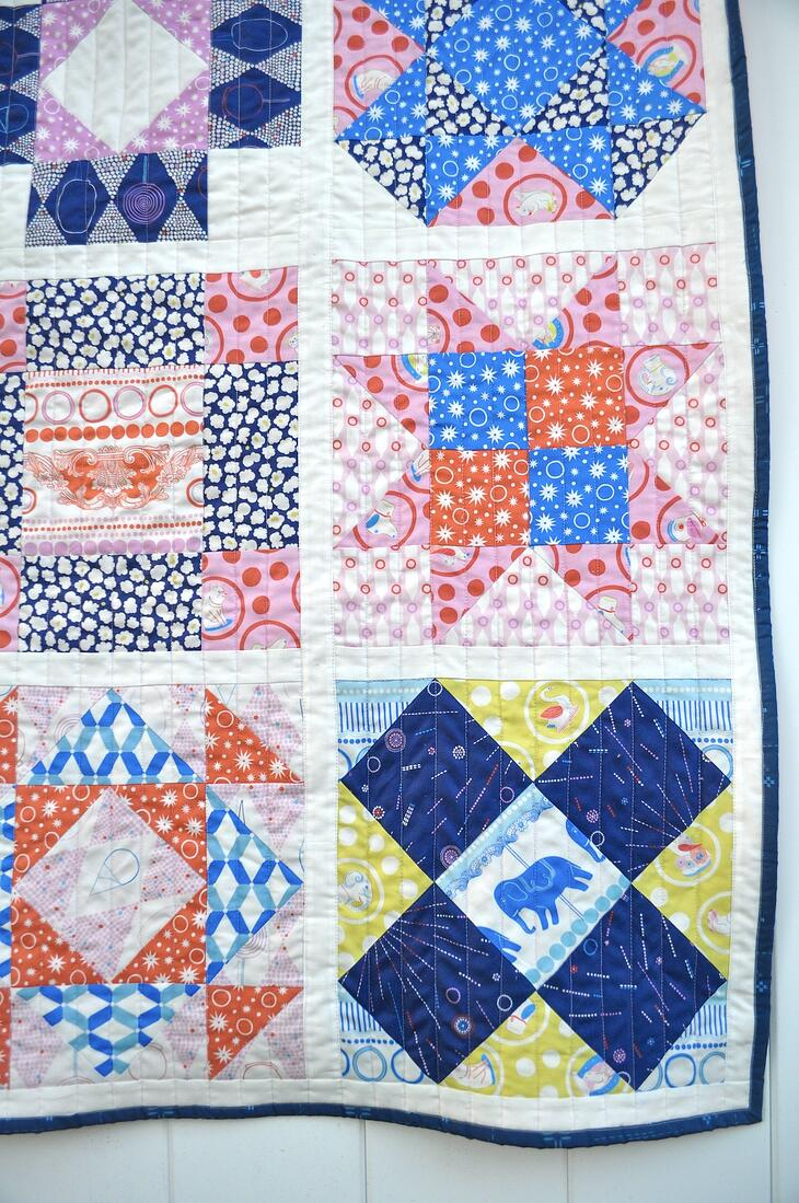 Ring Toss FIGO Fabrics Sampler quilt made with AccuQuilt GO! Qube 12 inch hung on fence