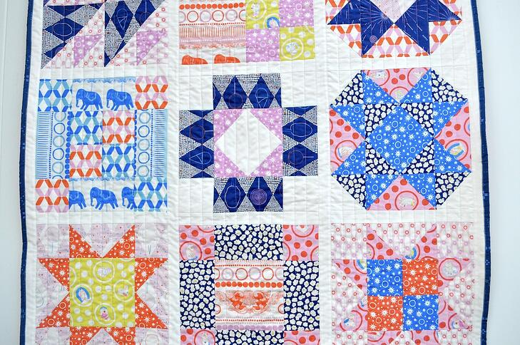 Close up of nine blocks within sampler quilt with triangles, squares and rectangles
