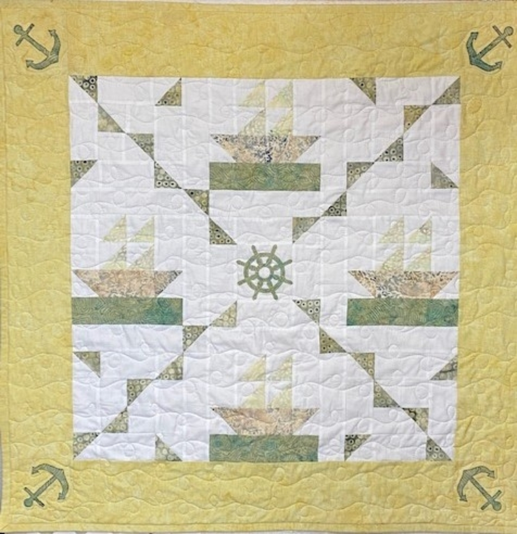 close up of green and yellow pieced sailboat baby quilt with anchor and ship wheel applique
