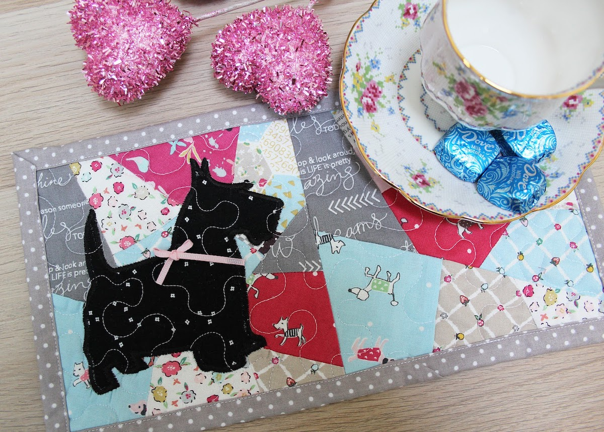 Double crazy quilt mug rug with Scottie dog applique next to tea cup.