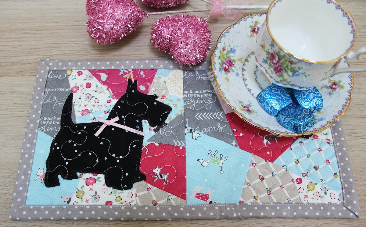 finished quilted mug rug with scottie dog applique on crazy quilt blocks with tea cup and Dove chocolate and pink glitter hearts on a wooden table