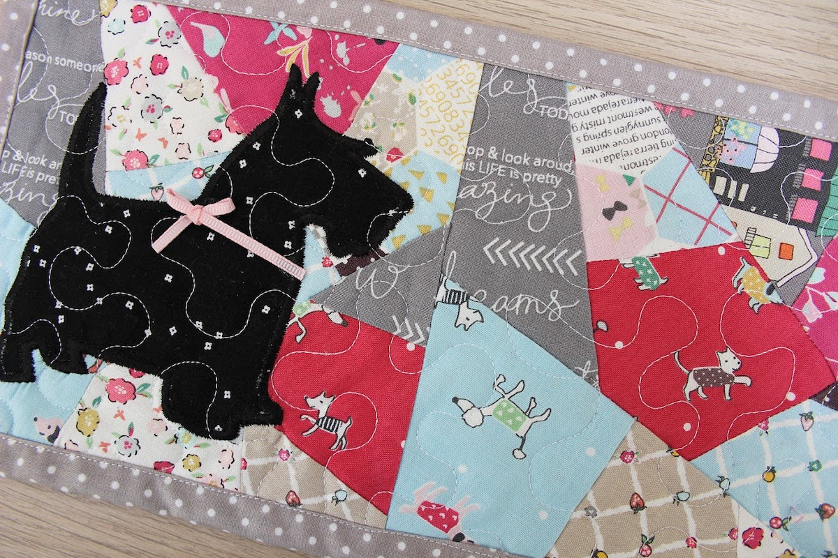close up of quilted mug rug with scottie dog applique on a crazy quilt block and stippling quilting