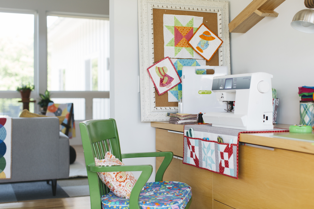 green chair in front of sewing machine and accuquilt fabric cutter in sewing room