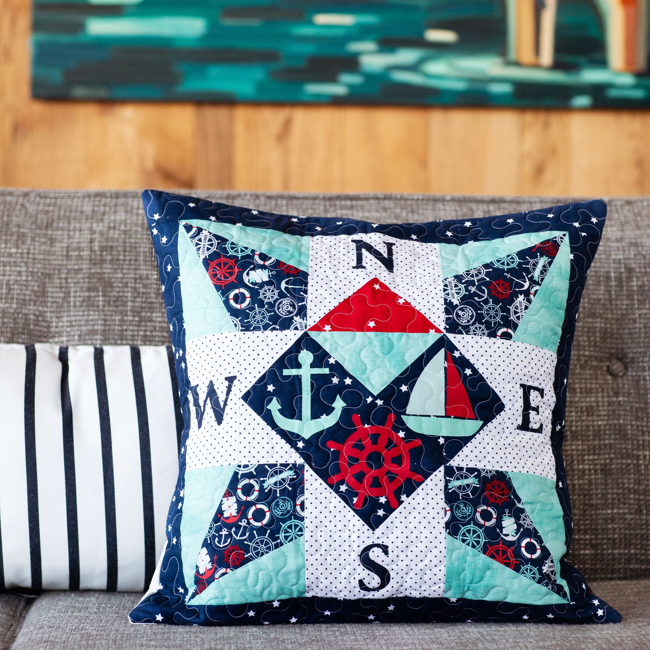 pieced oversized pillow with compass shape and nautical applique shapes on grey couch