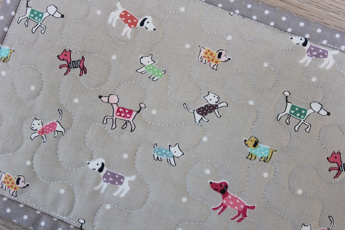 back of quilted mug rug with stipple quilt pattern and grey fabric with multicolored dogs in sweaters